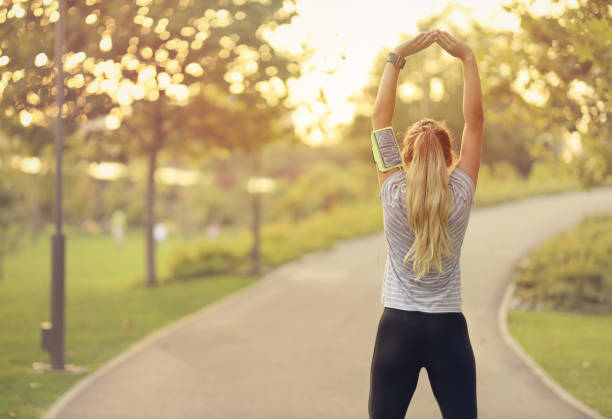 Fit young woman doing stretching exercises in the park stock photo