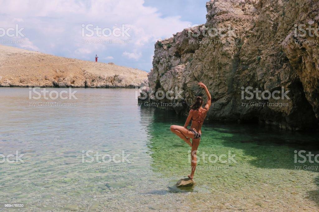 Fit junge Frau tut Yoga-Posen auf einem Felsen am Strand – Foto