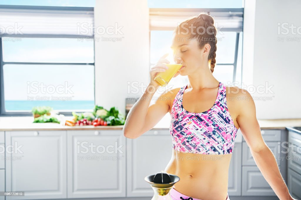 Fit young woman drinking fresh orange juice - Photo