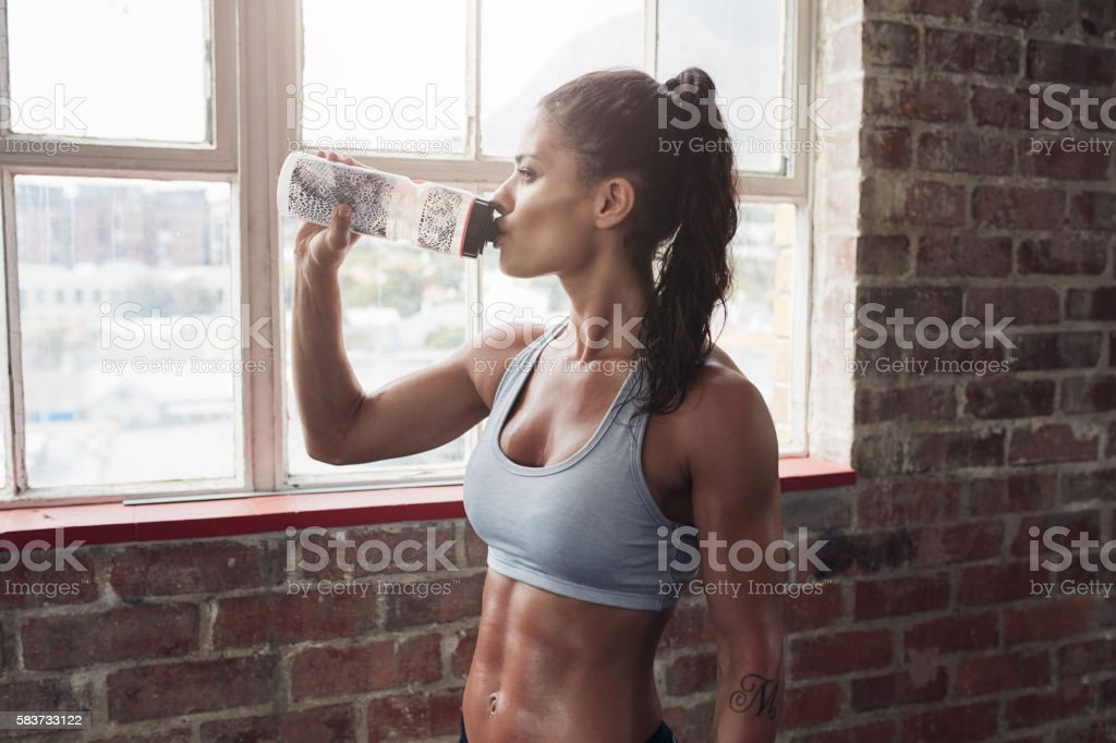 Fit young woman drinking water in the gym stock photo