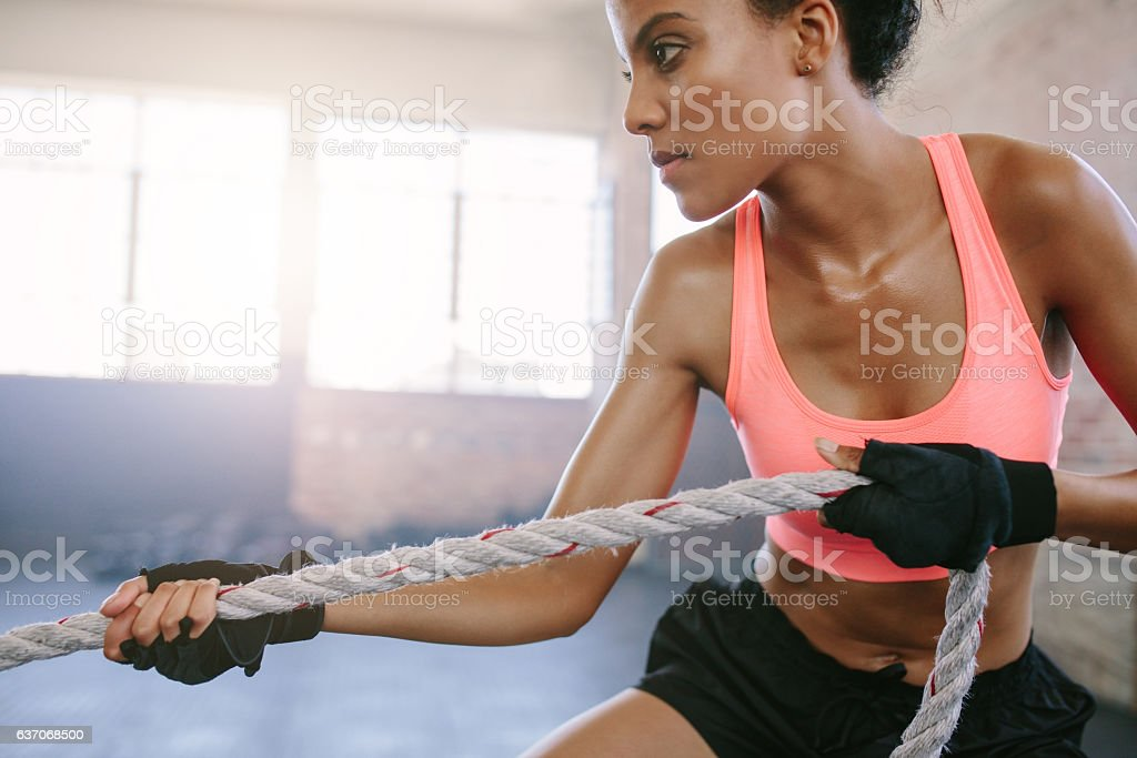 Fit young woman exercising with rope at a gym stock photo