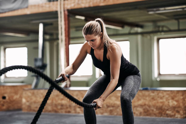 Fit young woman exercising with ropes during a gym workout stock photo