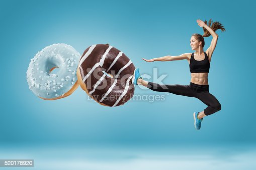 istock Fit young woman fighting off bad food on a blue 520178920