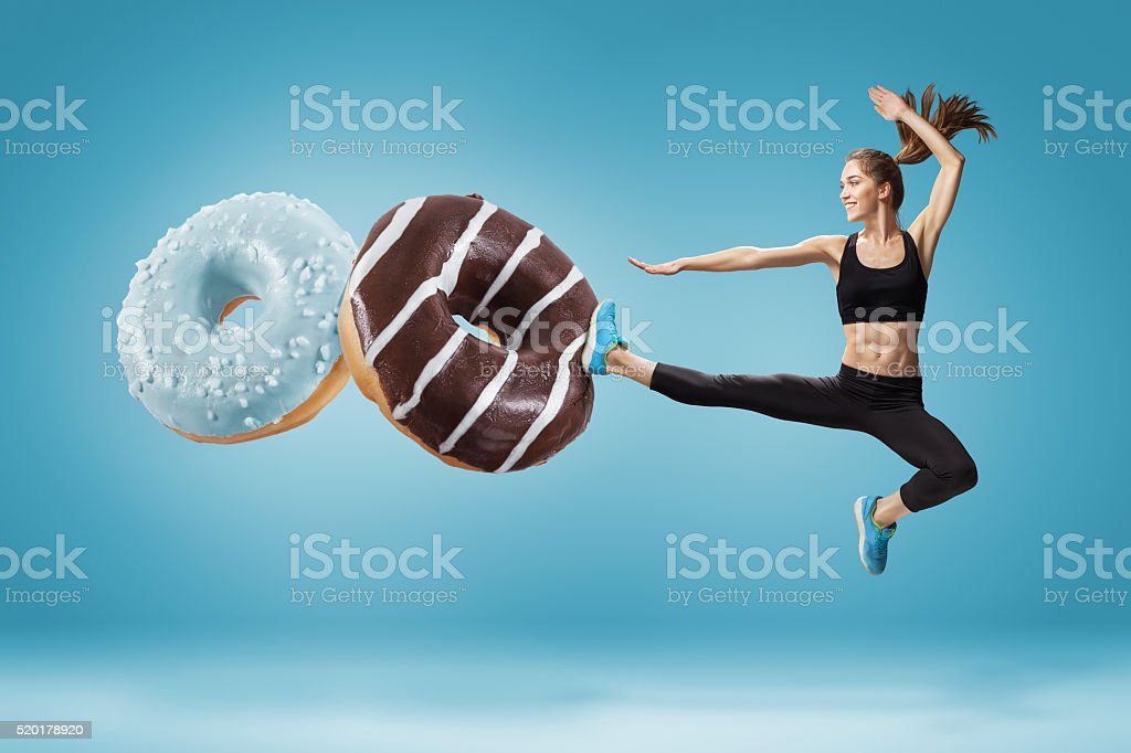 Fit young woman fighting off bad food on a blue stock photo