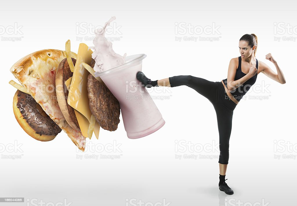 Fit young woman fighting off fast food royalty-free stock photo