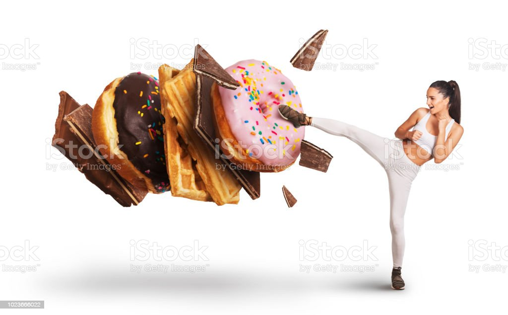 Fit young woman fighting off sweets and candy royalty-free stock photo