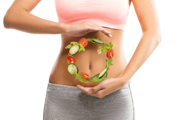 fit, young woman holding a circle made out of vegetables over her abdomen - stomach stock pictures, royalty-free photos & images