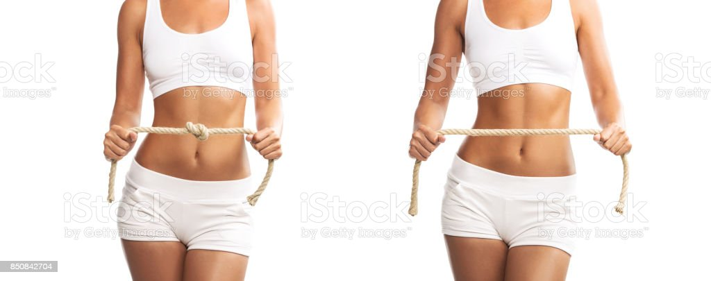 Fit young woman holding a tied and untied rope over her abdomen, isolated on white background stock photo