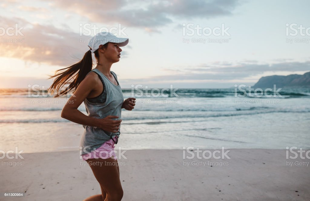 Fit young woman jogging at the beach in morning – Foto
