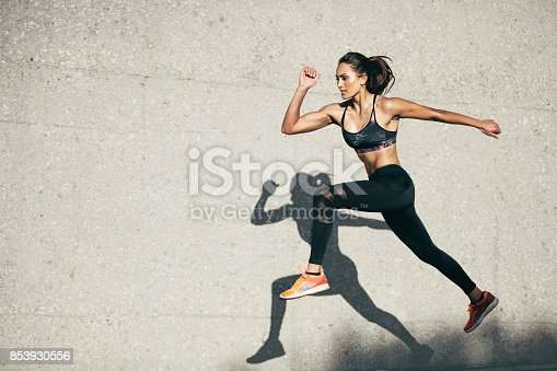 istock Fit young woman jumping and running 853930556