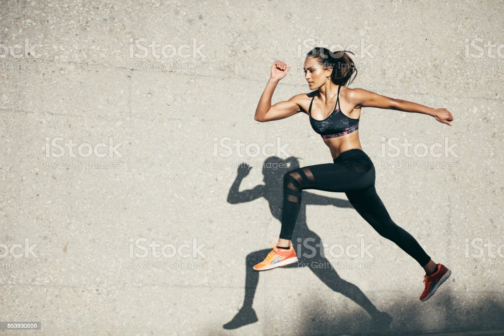 Fit young woman jumping and running - foto stock