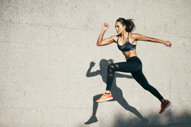 Fit young woman jumping and running stock photo