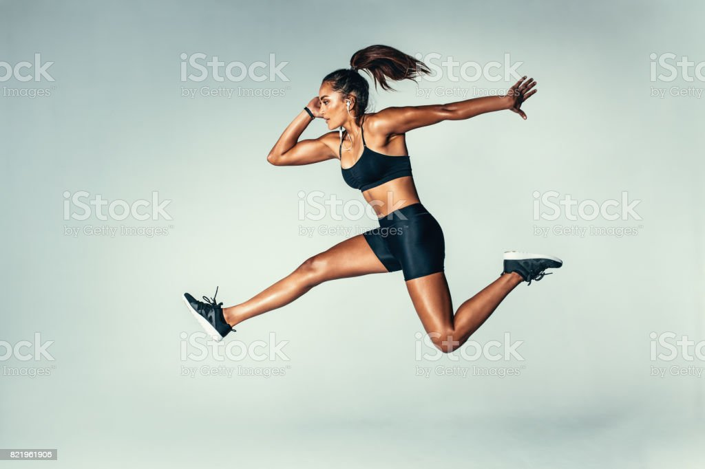 Fit young woman jumping in air stock photo