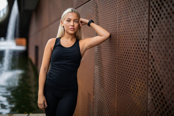 Fit Young Woman Leaning On Metallic Wall After Workout Portrait of fit young woman in sportswear leaning on metallic wall after workout tank top stock pictures, royalty-free photos & images