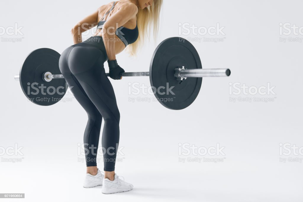 Fit young woman lifting barbell stock photo