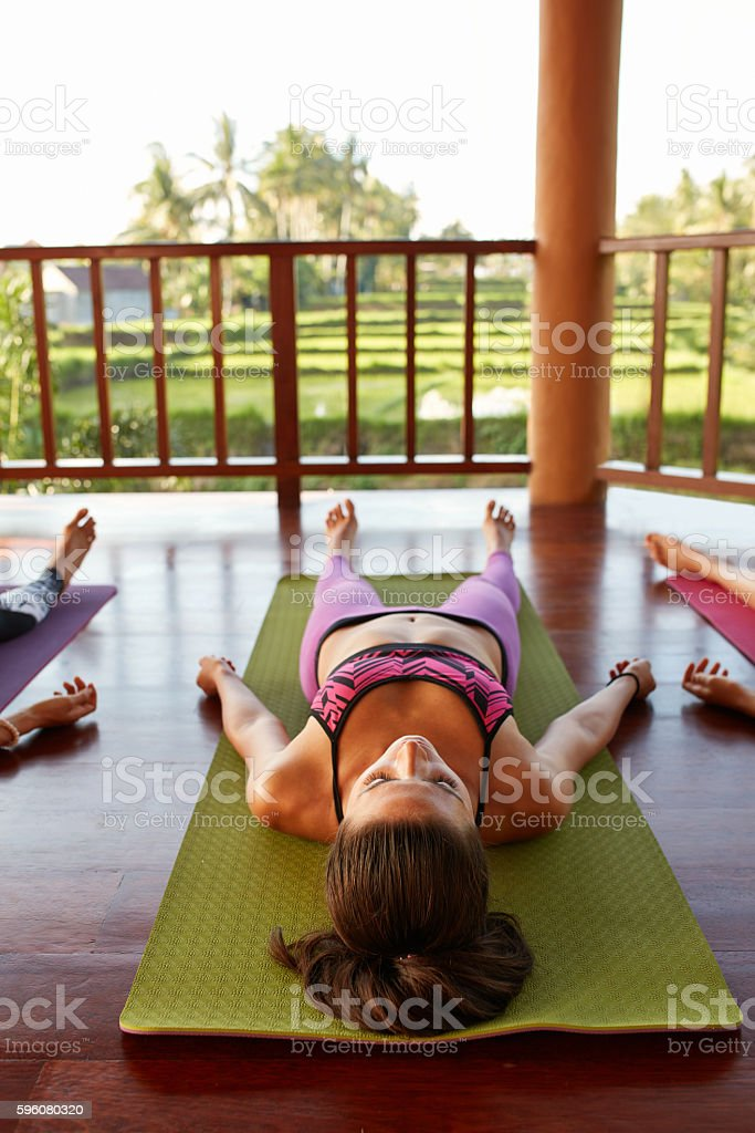 Fit young woman relaxing on yoga mat stock photo