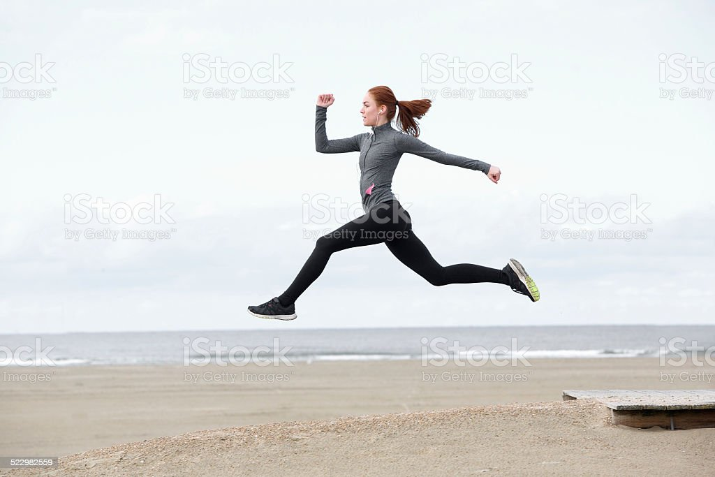 Fit young woman running and jumping stock photo