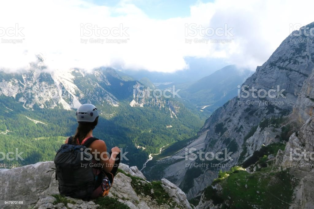 Fit young woman sitting and enjoying the valley view/ climbing/ via ferrata stock photo