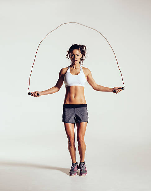 Fit young woman skipping rope stock photo