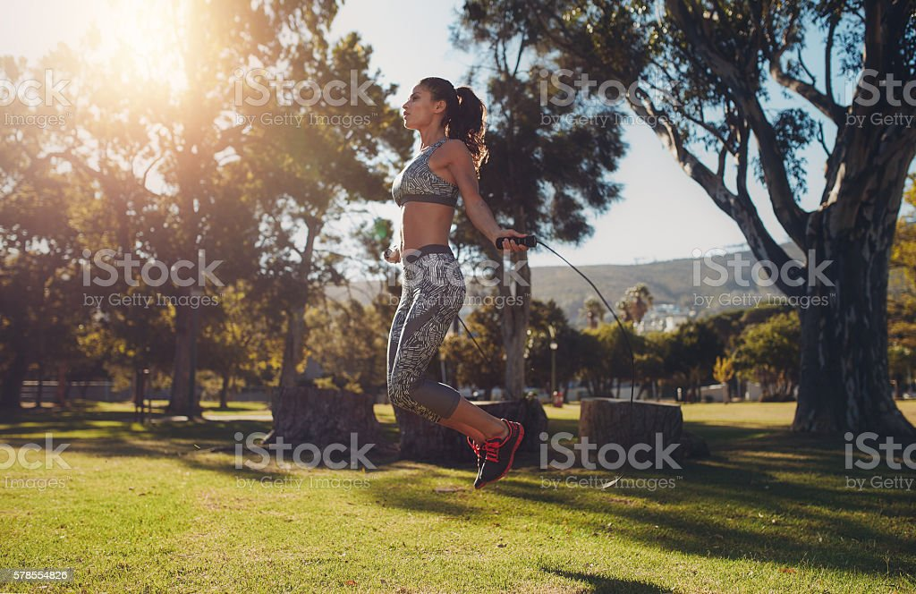 Fit young woman skipping with a jump rope stock photo