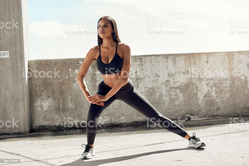 Fit young woman stretching zbiór zdjęć royalty-free