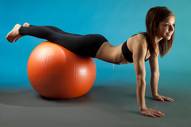 fit young woman training with exercise ball - black women wearing pantyhose stock photos and pictures