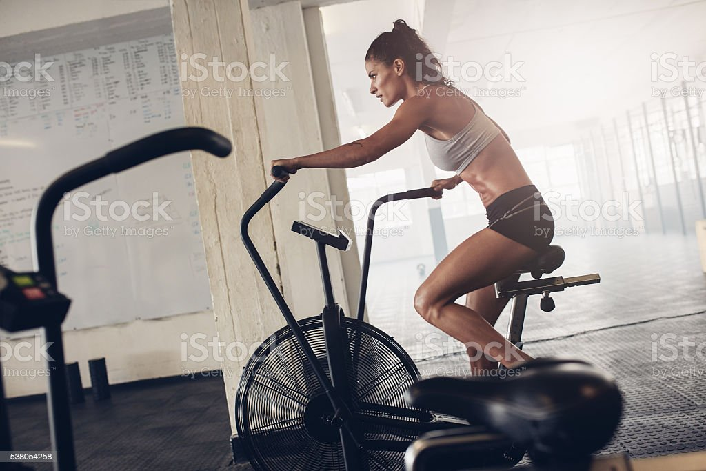 Fit young woman using exercise bike at the gym stock photo