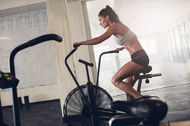 Fit young woman using exercise bike at the gym Fit young woman using exercise bike at the gym. Fitness female using air bike for cardio workout at gym gym. exercise bike stock pictures, royalty-free photos & images