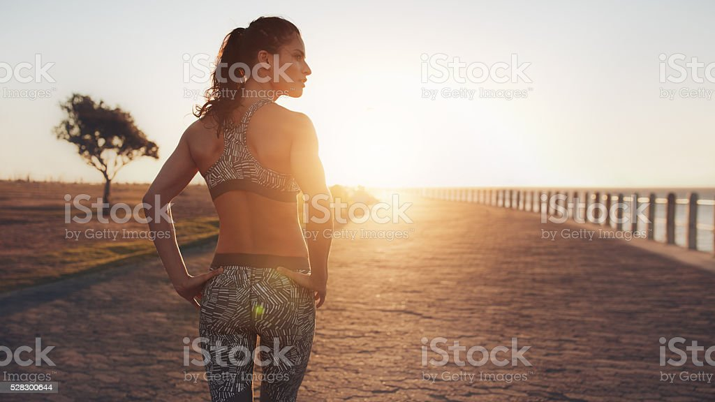 Fit young woman walking on seaside promenade stock photo