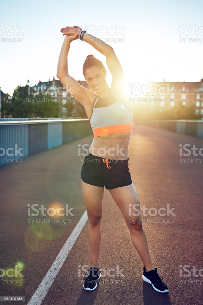 Fit young woman warming up before a workout stock photo