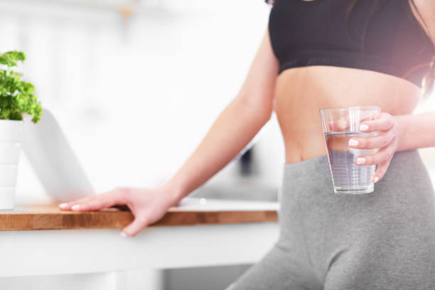 Fit young woman with glass of water in modern kitchen stock photo