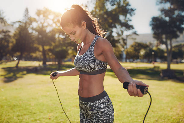 Fit young woman with jump rope in a park stock photo
