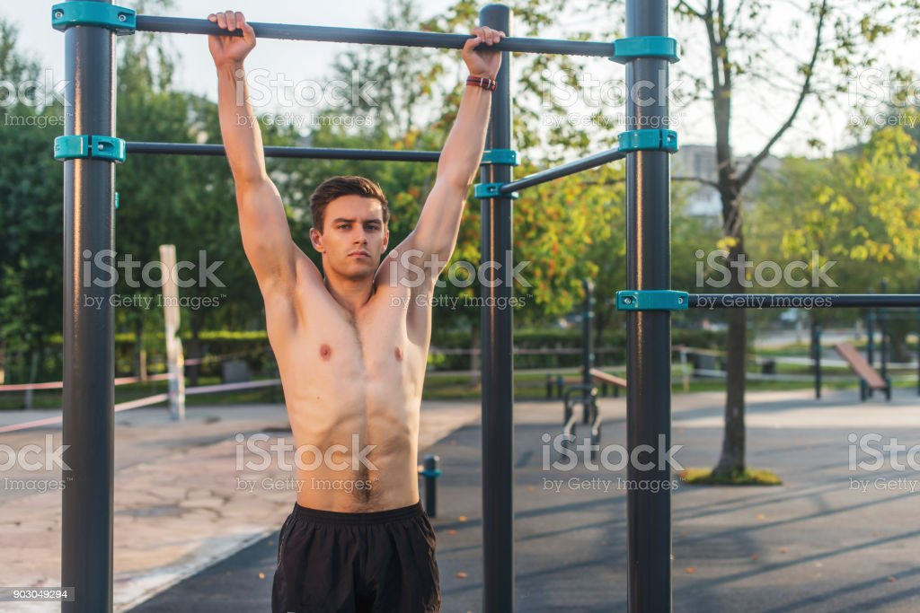 Fitnes man hanging on wall bars. Core cross training working out abs muscles stock photo