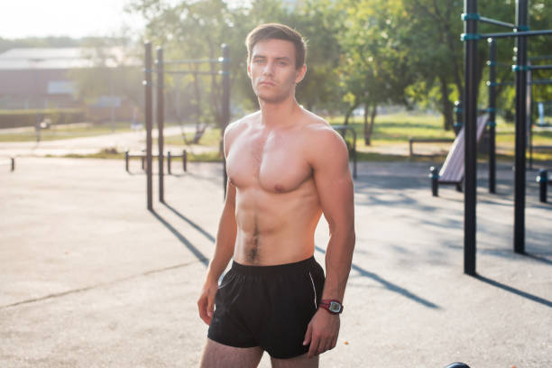 Fitnes man posing on street fitness station showing his muscular body stock photo
