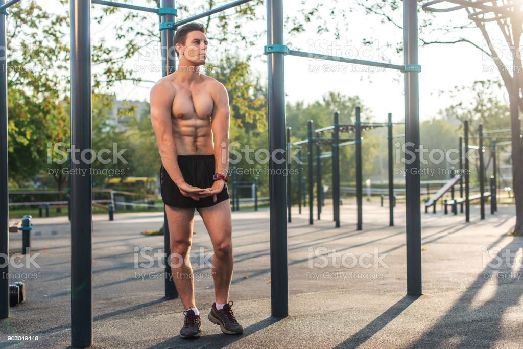 Fitnes man posing on street fitness station showing his muscular body Full lenght portrait. stock photo