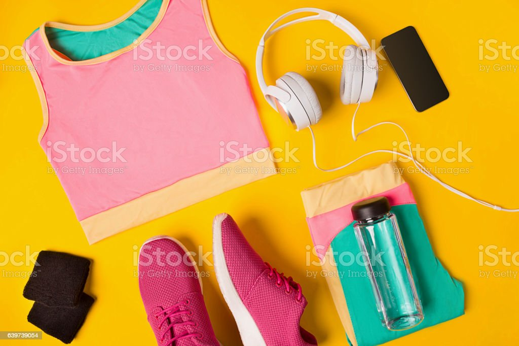 Fitness accessories on a yellow background. Sneakers, bottle of water stock photo