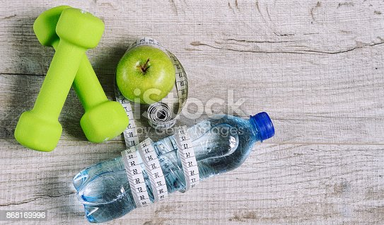 616251000 istock photo Fitness accessories. Sports dumbbells sneakers sports shoes and 868169996