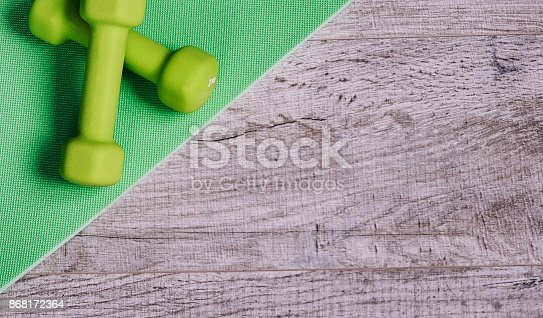 616251000 istock photo Fitness accessories. Sports dumbbells sneakers sports shoes and 868172364