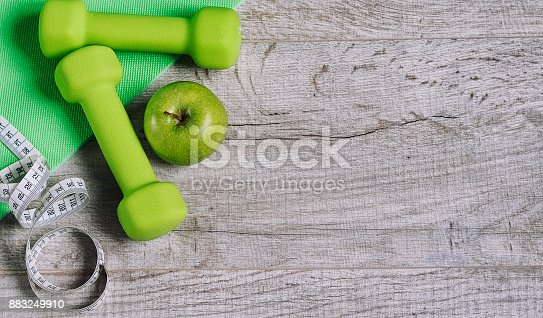 616251000 istock photo Fitness accessories. Sports dumbbells sneakers sports shoes and 883249910