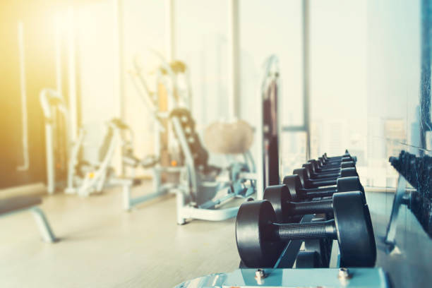 fitness and healthy background concept. dumbbells with blurred gym or sport club background at sunset. picture for add text message. backdrop for design art work. - health club stock photos and pictures