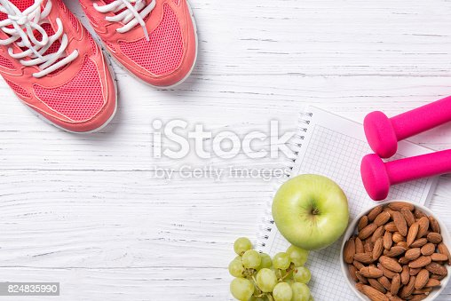 istock Fitness and healthy eating concept, pink sneakers and dumbbells with apple, grapes and almond nuts on notepad, wooden background, top view with copy space 824835990