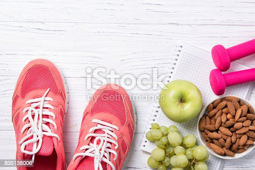 istock Fitness and healthy eating concept, pink sneakers and dumbbells with apple, grapes and almond nuts on notepad, wooden background, top view with copy space 835138006