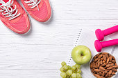 istock Fitness and healthy eating concept, pink sneakers and dumbbells with apple, grapes and almond nuts on notepad, wooden background, top view with copy space 835138826