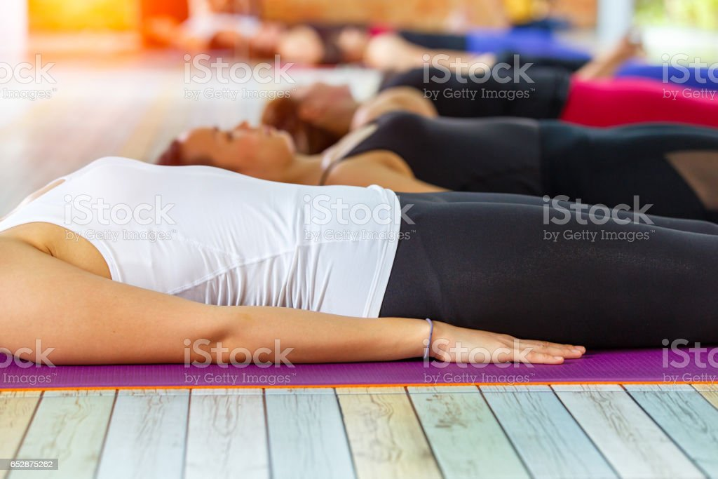 Fitness asian female group doing practicing in a yoga studio. Shavasana or corps pose is the end of a yoga class or practice. stock photo