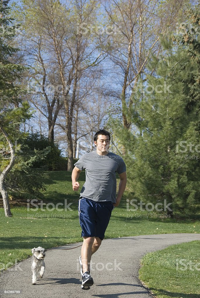 asian man running in the park with his dog