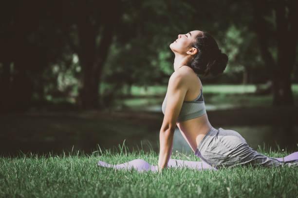 健身亞洲婦女做瑜伽在公園 - 瑜珈 個照片及圖片檔