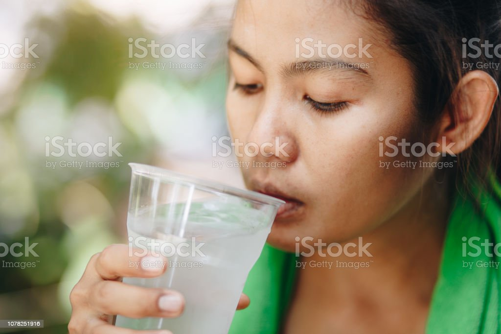 fitness athlete asian woman drinking water from plastic glass
