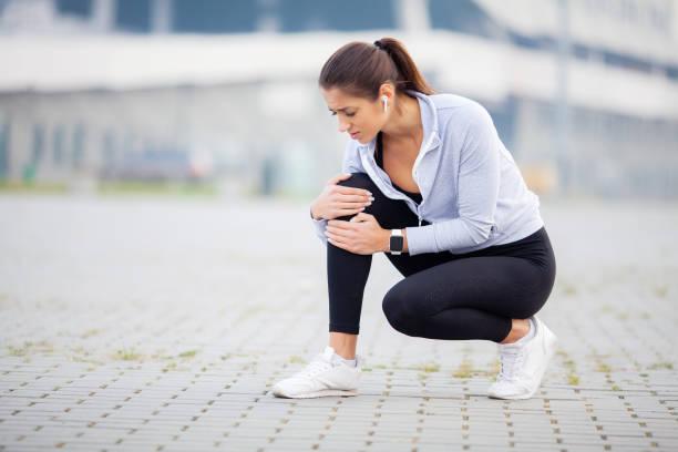 aptidão. mulheres atléticas segurando o joelho ter um trauma - articulação humana - fotografias e filmes do acervo