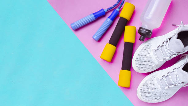 Fitness background of Equipment for gym and home, Sports shoes, Jump rope, dumbbells, mat, water on pastel blue and pink background and notebook top view for copy space