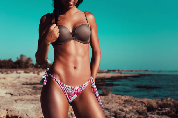 Fitness beach woman posing in the sun showing her fit body stock photo